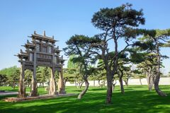 Traditional archway building with meadow and pine tree
