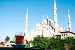 Traditional aromatic Turkish black tea in a tulip-shaped glass. In the background, the Blue Mosque is also called Stock Images