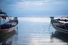 Traditional asian boats in sea during sunset directed towards the horizon Royalty Free Stock Image