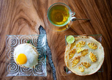 Traditional Asian Breakfast, rice with egg, pancake with pineapple and tea on wooden table. Traditional Asian Breakfast, rice with egg, pancake with pineapple Stock Image