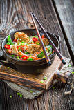 Traditional asian dish with chicken with sesame and noodles. On old wooden table royalty free stock photography