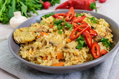 A traditional Asian dish - pilaf with meat, mushrooms and pepper capi in a bowl Stock Image