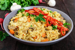 A traditional Asian dish - pilaf with meat, mushrooms and pepper capi in a bowl Royalty Free Stock Image