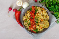A traditional Asian dish - pilaf with meat, mushrooms and pepper capi in a bowl Stock Photo