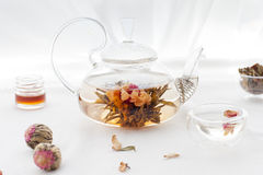Traditional asian floral tea in a glass teapot. On white textile background stock photo