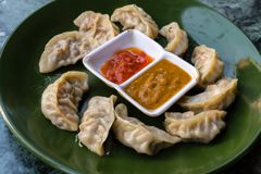 Traditional asian food. Nepalese steamed dumpling momo served with tomato chutney stock images