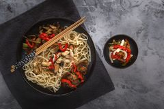 Traditional Asian food - noodles with seafood, salad, red pepper and fried mushrooms are on a gray table. Copy space. Top view royalty free stock images