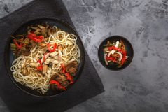 Traditional Asian food - noodles with seafood, salad, red pepper and fried mushrooms are on a gray table. Copy space. Top view royalty free stock photo