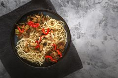 Traditional Asian food - noodles with seafood, salad, red pepper and fried mushrooms are on a gray table. Copy space. Top view royalty free stock photography