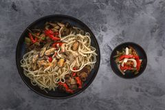 Traditional Asian food - noodles with seafood, salad, red pepper and fried mushrooms are on a gray table. Copy space. Top view stock photos