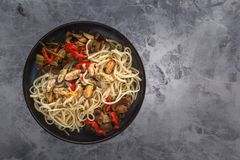 Traditional Asian food - noodles with seafood, salad, red pepper and fried mushrooms are on a gray table. Copy space. Top view royalty free stock image
