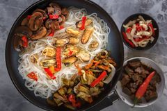 Traditional Asian food - rice noodles with seafood, salad, red pepper and fried mushrooms are on a gray table. Close-up. Top view royalty free stock photography