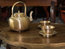 Traditional Asian Golden Teapot and Cups on Little Wooden Table Royalty Free Stock Photography