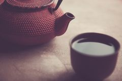 Traditional asian  red iron teapot  horyzontal image. Traditional asian iron teapot with clay cup full of tea Stock Photo