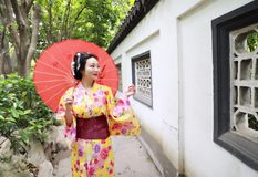 Traditional Asian Japanese beautiful bride Geisha woman wears kimono hold a white red umbrella in a summer nature garden. Japanese woman with kimono Japanese Stock Image