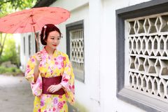 Traditional Asian Japanese beautiful Geisha bride woman wears kimono hold a umbrella in a summer nature garden. Japanese woman with kimono Japanese bride smiling Royalty Free Stock Photo
