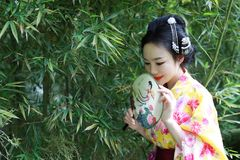 Traditional Asian Japanese beautiful Geisha woman bride wears kimono hold a fan in a summer nature. Japanese woman with kimono Japanese bride smiling stand by Royalty Free Stock Photo