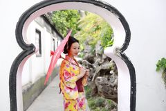 Traditional Asian Japanese beautiful Geisha woman bride wears kimono hold a umbrella in a summer nature. Japanese woman with kimono Japanese bride smiling stand Royalty Free Stock Photos