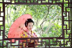 Traditional Asian Japanese beautiful Geisha woman bride wears kimono with red umbrella on hand in a summer nature. Japanese woman with kimono Japanese bride Royalty Free Stock Photography