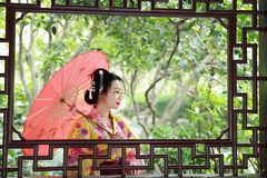 Traditional Asian Japanese beautiful Geisha woman bride wears kimono with red umbrella on hand in a summer nature. Japanese woman with kimono Japanese bride Royalty Free Stock Photos