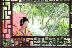 Traditional Asian Japanese beautiful Geisha woman bride wears kimono with red umbrella on hand in a summer nature. Japanese woman with kimono Japanese bride Stock Photos