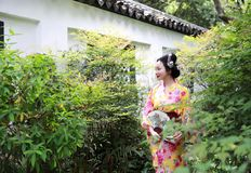 Traditional Asian Japanese beautiful Geisha woman wears kimono with a fan on hand in a summer nature. Japanese woman with kimono Japanese bride smiling stand by Royalty Free Stock Photos