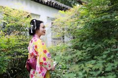 Traditional Asian Japanese beautiful Geisha woman wears kimono with a fan on hand in a summer nature. Japanese woman with kimono Japanese bride smiling stand by Royalty Free Stock Photo