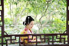 Traditional Asian Japanese beautiful Geisha woman wears kimono with a fan on hand in a summer nature. Japanese woman with kimono Japanese bride smiling stand by Stock Photos
