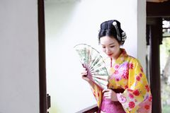 Traditional Asian Japanese beautiful Geisha woman wears kimono hold a fan sit in a summer nature garden. Japanese woman with kimono Japanese bride smiling stand Stock Image