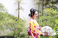 Traditional Asian Japanese beautiful Geisha woman wears kimono hold a fan sit in a summer nature garden. Japanese woman with kimono Japanese bride smiling stand Stock Photography