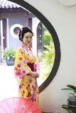 Traditional Asian Japanese beautiful Geisha woman wears kimono hold a umbrella on hand in a summer nature. Japanese woman with kimono Japanese bride smiling Stock Photos