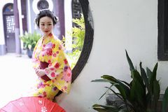 Traditional Asian Japanese beautiful Geisha woman wears kimono hold a umbrella on hand in a summer nature. Japanese woman with kimono Japanese bride smiling Royalty Free Stock Images