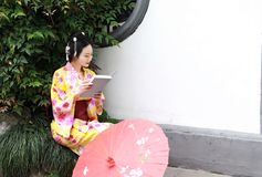 Traditional Asian Japanese beautiful Geisha woman wears kimono hold a umbrella reading book in a summer nature. Japanese woman with kimono Japanese bride smiling Royalty Free Stock Photo