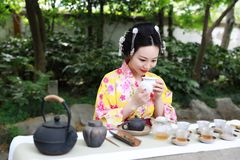 Traditional Asian Japanese beautiful Geisha woman wears kimono show tea art ceremony drink tea in a summer spring outdorr garden Royalty Free Stock Photo