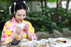 Traditional Asian Japanese beautiful Geisha woman wears kimono show tea art ceremony drink tea in a summer spring outdorr garden Royalty Free Stock Photos