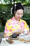 Traditional Asian Japanese beautiful Geisha woman wears kimono show tea art ceremony drink tea in a summer spring outdorr garden. Japanese woman with kimono Stock Photo