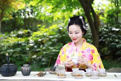 Traditional Asian Japanese beautiful Geisha woman wears kimono show tea art and ceremony in a summer nature. Japanese woman with kimono Japanese bride smiling Royalty Free Stock Photos