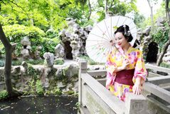 Traditional Asian Japanese beautiful woman bride wears kimono with white umbrella stand by bamboo in outdoor spring garden. Japanese woman with kimono Japanese Stock Images