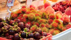 Traditional asian market. Stall full of fresh rambutans and mangostines Royalty Free Stock Photo