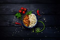 Traditional asian noodle lagman with vegetables and meat. Top view dark wooden background Royalty Free Stock Photo