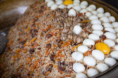 Traditional Asian pilaf with beef and chicken eggs. A large cauldron, rice devzira, cumin spices, cotton seed oil. The famous dish Royalty Free Stock Images