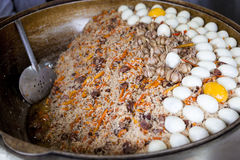 Traditional Asian pilaf with beef and chicken eggs. A large cauldron, rice devzira, cumin spices, cotton seed oil. The famous dish Royalty Free Stock Image