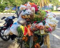 Traditional Asian street food in Bali - motorbike is hung with packages with different snacks stock photography