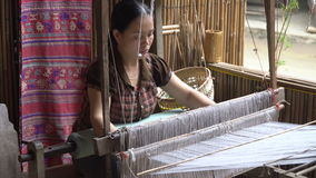 Traditional asian textile manufacture in craft village. Woman working with a waist loom to finish an handcraft to sell in the market. Traditional asian textile stock video footage