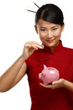 Traditional asian woman save a coin in a piggybank Royalty Free Stock Images