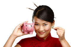 Traditional asian woman save a coin in a piggybank Royalty Free Stock Image