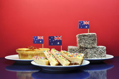 Traditional Australian food - meat pie and sauce, lamingtons and fairy bread - with flag Royalty Free Stock Photos