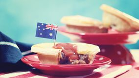 Traditional Australian Meat Pies for Australia Day celebration, vintage wash. Traditional Australian Meat Pies for Australia or Anzac Day holiday party food, in royalty free stock image