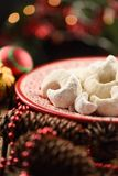 Traditional Austrian Christmas pastry: vanilla crescent vanillekipferl. Homemade nut cookies in icing sugar on red plate decorated royalty free stock photos