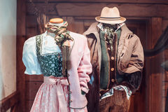 Traditional austrian clothes for male and female exposed in Salzburg store showcase. Female dress and male costume of pastel colours Stock Photos
